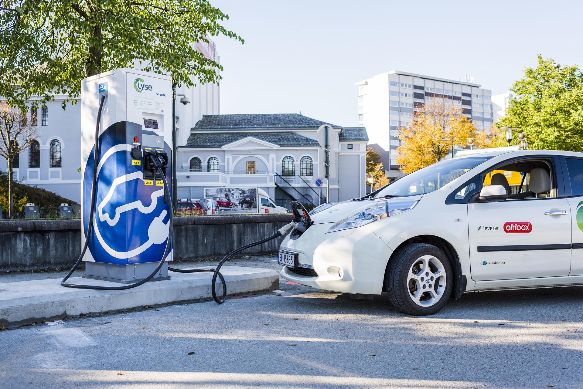 Hvit elbil står til lading på hurtigladestasjon i Stavanger.