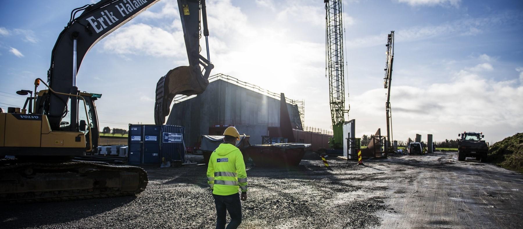 Gravemaskin står på byggeplass hvor et nytt bygg er under oppførelse. Foto Fredrik Ringe