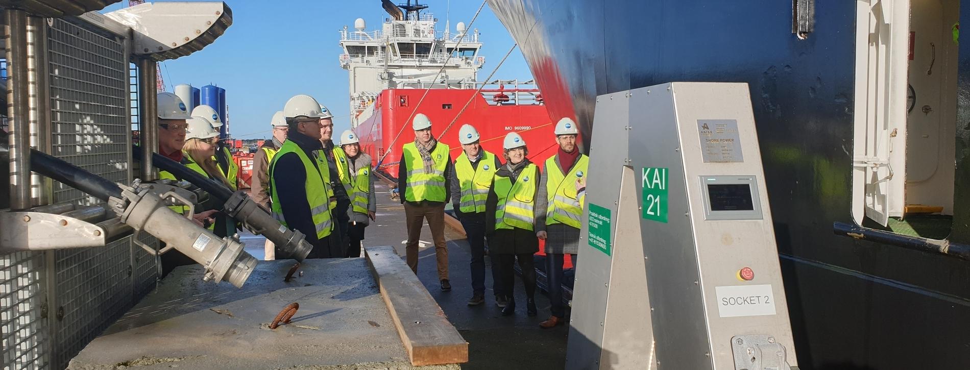 På kaien står deltakere i Elnett21 sammen med journalister i gule vester og hvite hjelmer ved siden av landstrømanlegget. Et rødt offshorefartøy ligger til kai bak dem.