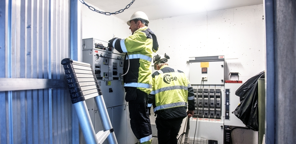 To montører i gult verneutstyr arbeider i en nettstasjon. Foto Fredrik Ringe