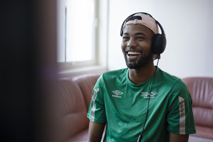 Idris som spiller dataspill med headset på hodet.