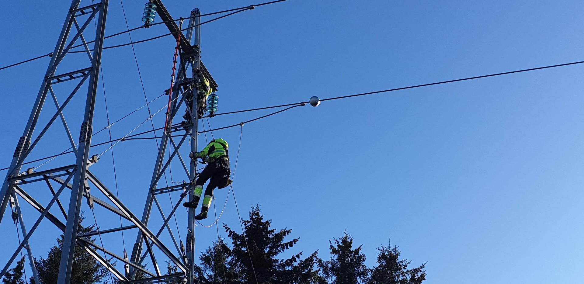 To montører klatrer ned masten etter å ha fått plassert en sensorkule på kraftlinjen.