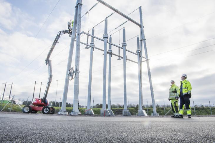 To ansatte i gule jakker studerer arbeidet som gjøres på kraftlinjen som går inn til strømmasten som er satt opp ved transformatorstasjonen på Opstad.