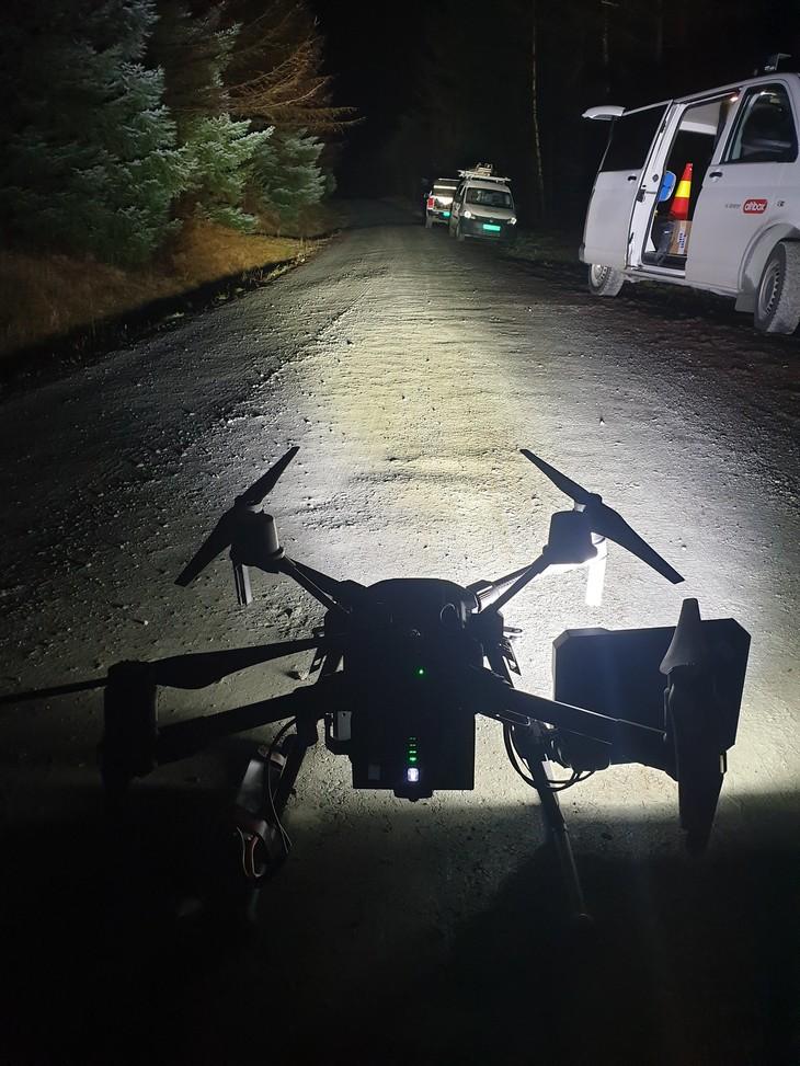 Drone står på grusveien og lyser denne opp. Langs kanten står flere montørbiler.