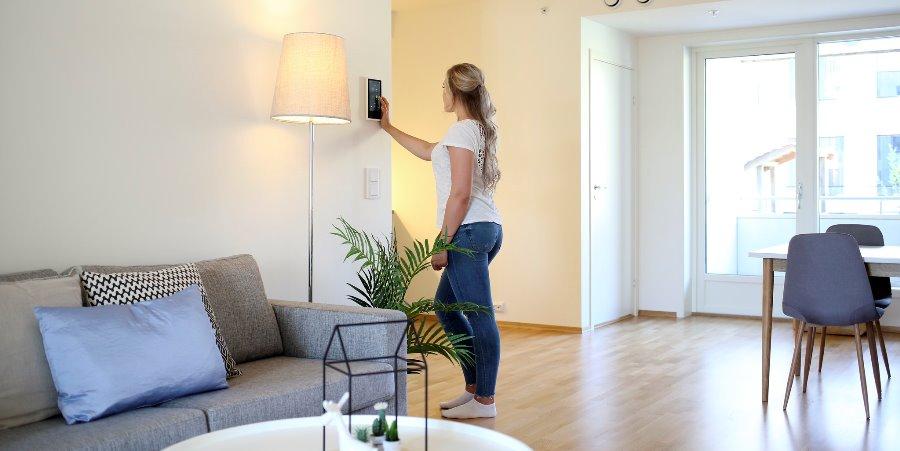 Ung kvinne styrer strømforbruket via et panel på veggen i stuen.