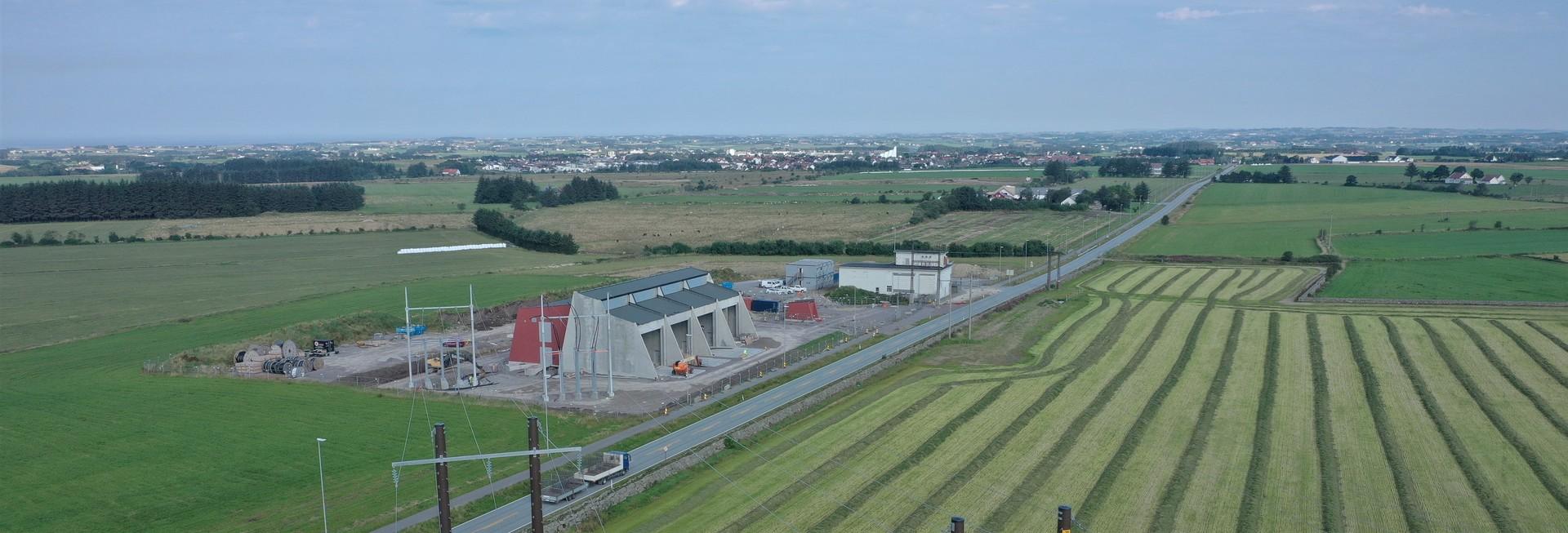 Nye Opstad transformatorstasjon med framside i grå betong, sett fra luften med grønne marker omkring. Gårder og boliger i bakgrunnen.
