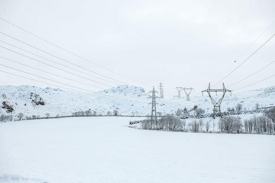 To kraftlinjer går parallelt ned over en snøkledd høyde. Foto Fredrik Ringe