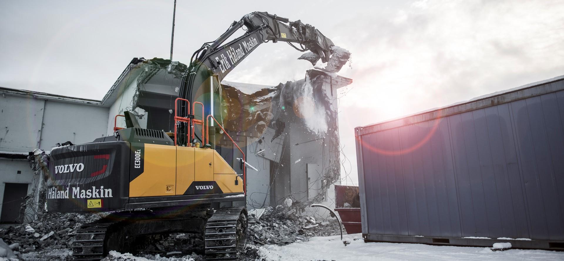Gravemaskin er i sving med å rive betongvegg og tak på en gammel transformatorstasjon.
