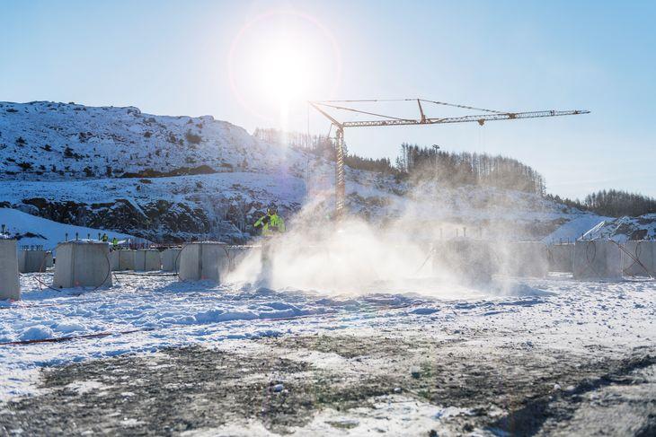 Snø og is spruter rundt en ansatt som arbeider ved siden av mange små betongfundamenter på nye Fagrafjell transformatorstasjon