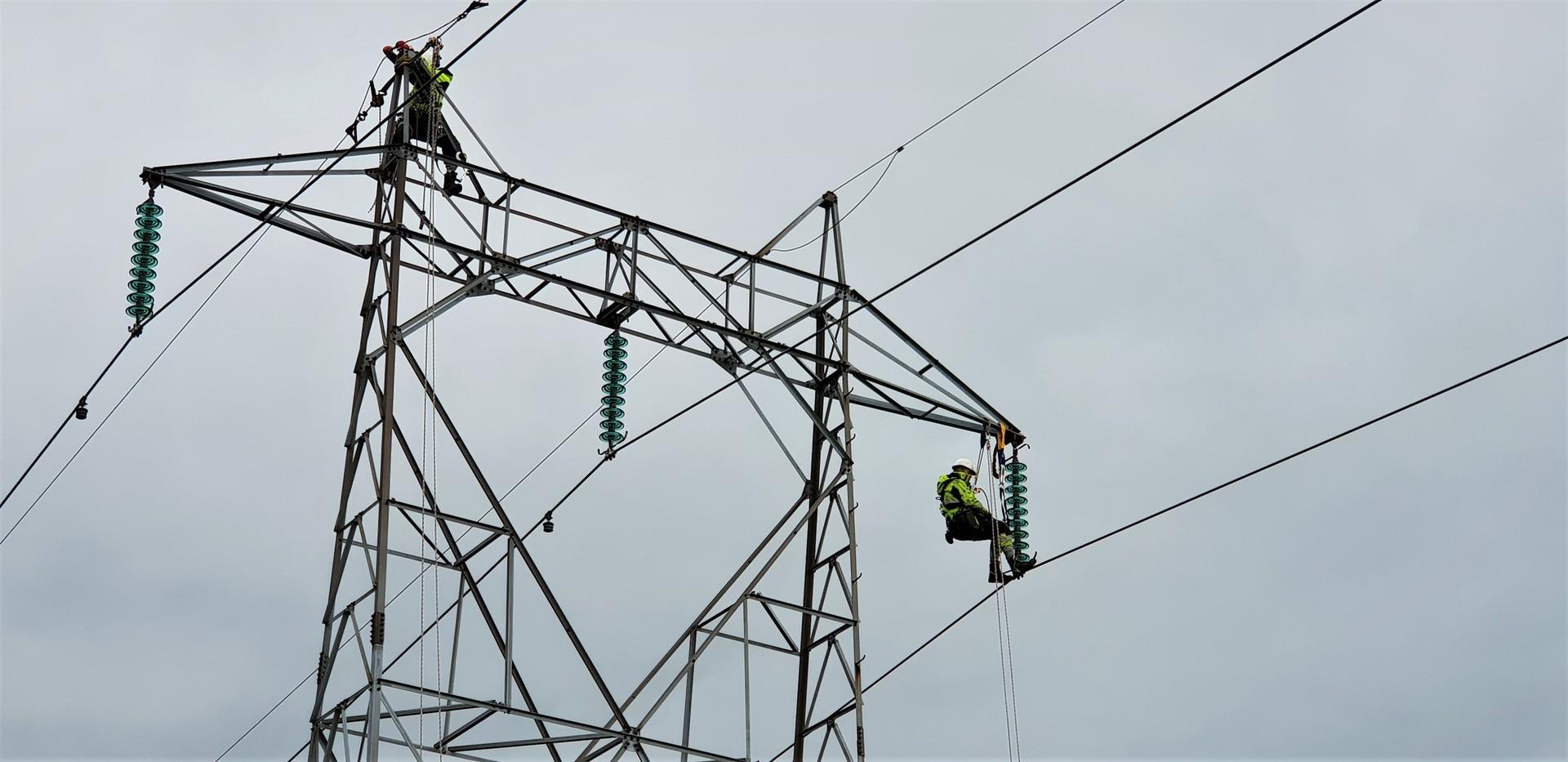 To montører står på hver sin side i toppen av en strømmast og monterer nye komponenter.