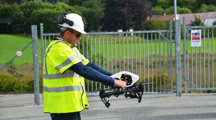 Drone holdes stødig av ansatt før den føres opp i luften.