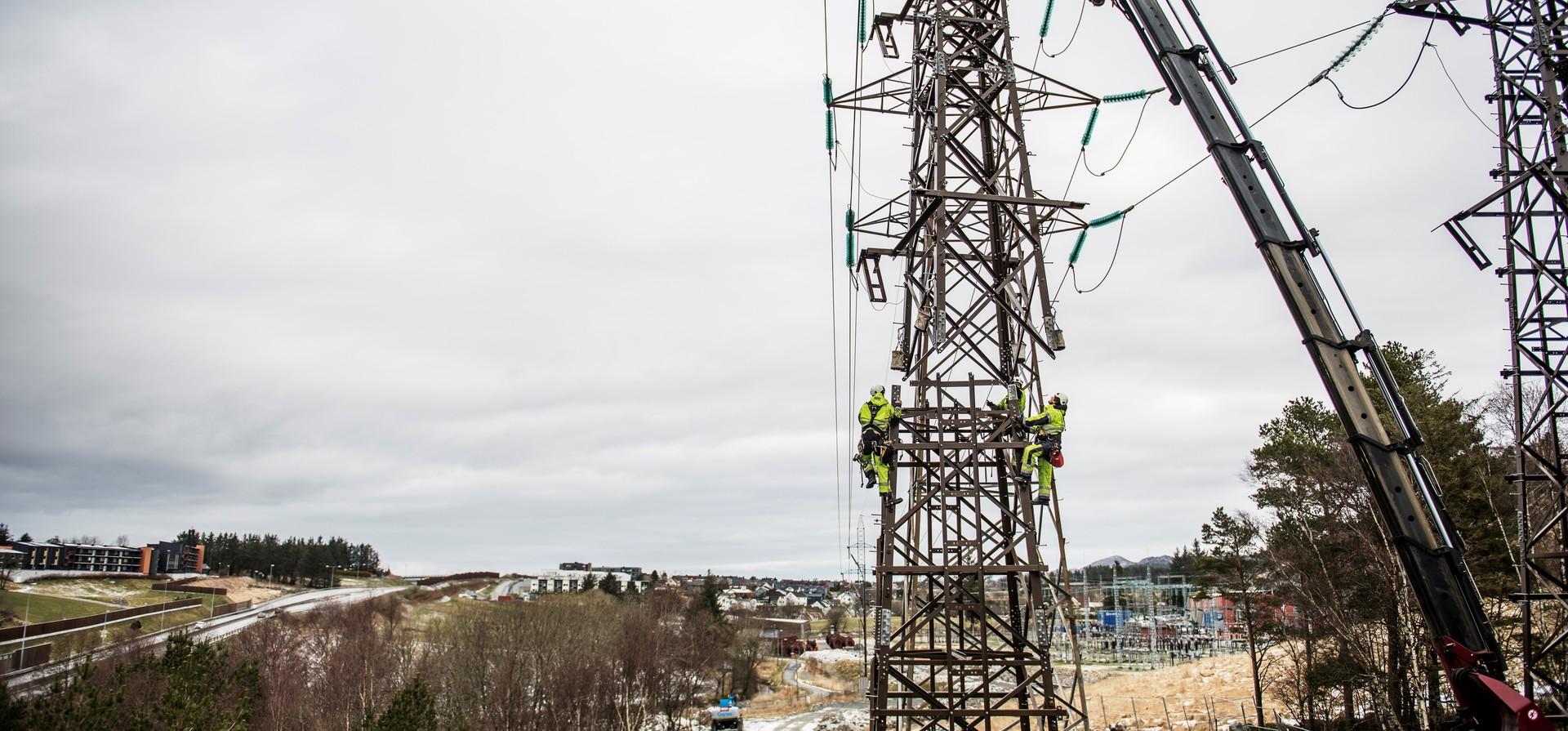 Montører står i en strømmast, mens øverste del av ny mast blir heist på plass.