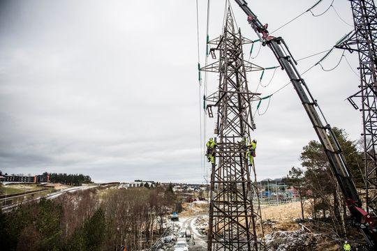 Montører står i strømmast, mens siste del på den nye masten heises på plass